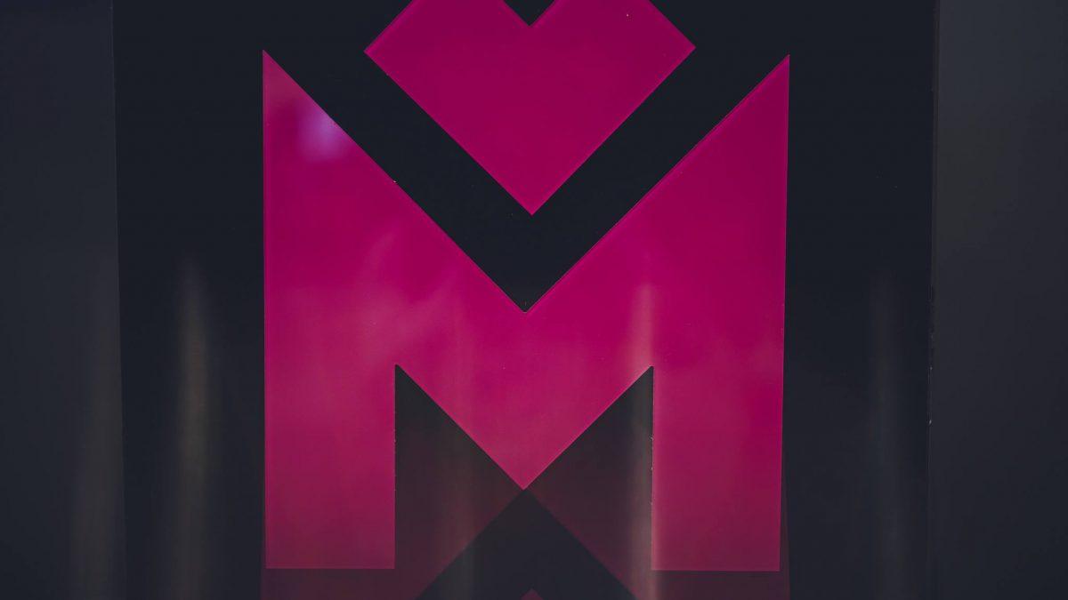 Litera M w kolorze fuksji na czarnym tle