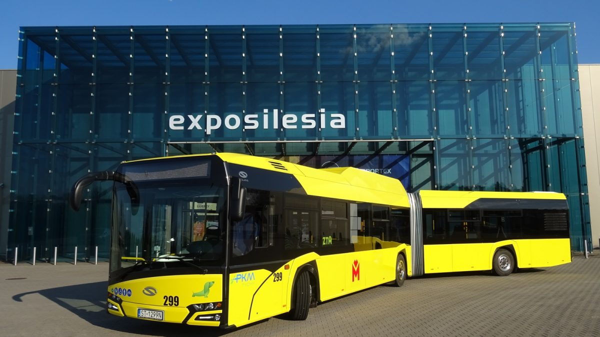 Żółty autobus, w tle oszklony budynek