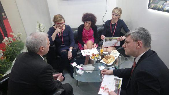 Pięć osób negocjujących przy stole