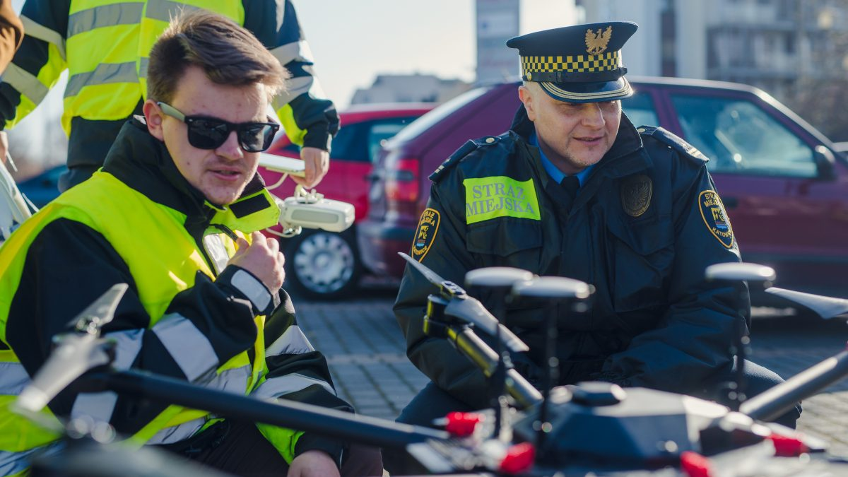 Strażnik miejski i operator drona przygotowujący maszynę do lotu