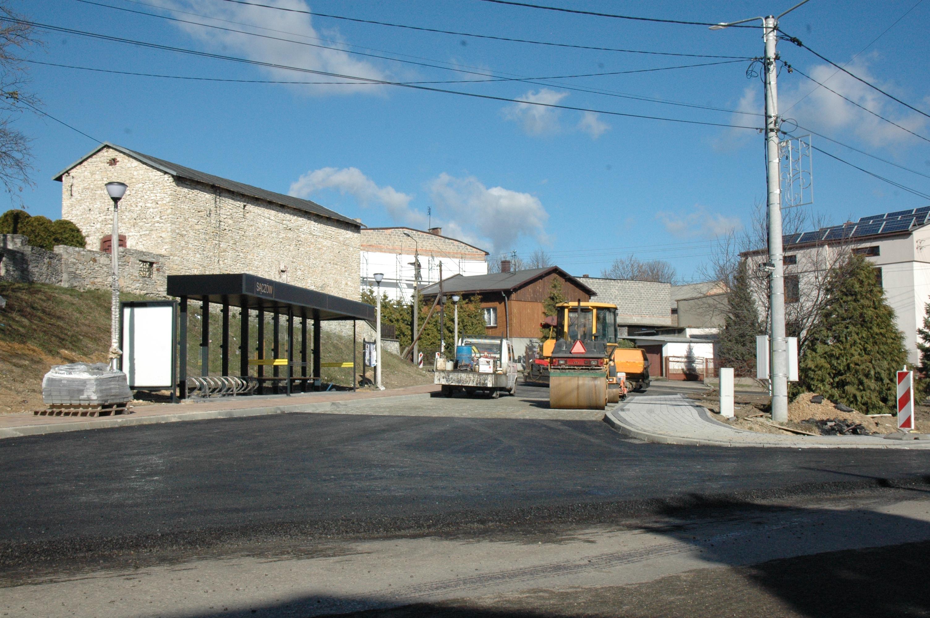 Remont drogi, na środku obok siebie stoją samochód oraz walec, po lewej stronie znajduje się przystanek autobusowy