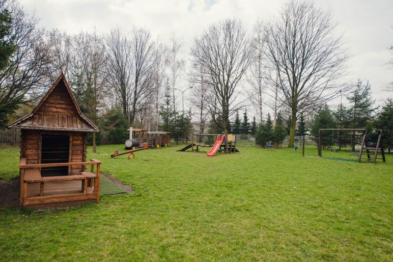 Elementy placu zabaw jak drewniane domki, huśtawki, zjeżdżalnie, w tle rosną drzewa