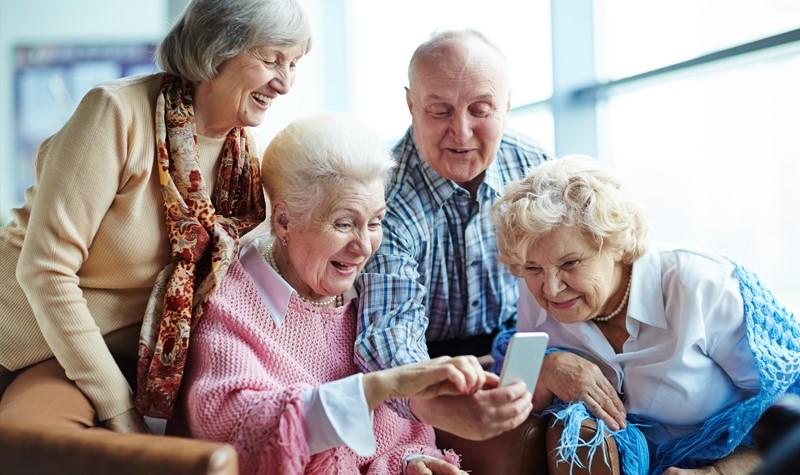 Grupa czterech seniorów obserwuje ekran smartfona