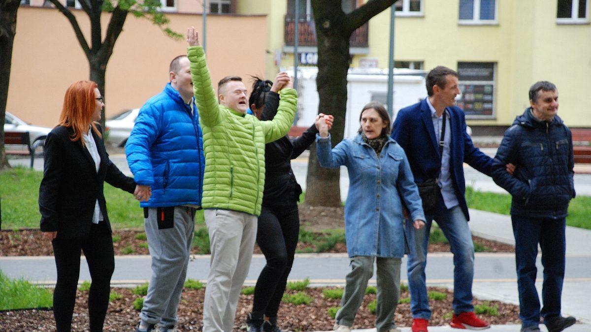 Osoby niepełnosprawne trzymające się za ręce podczas imprezy integracyjnej