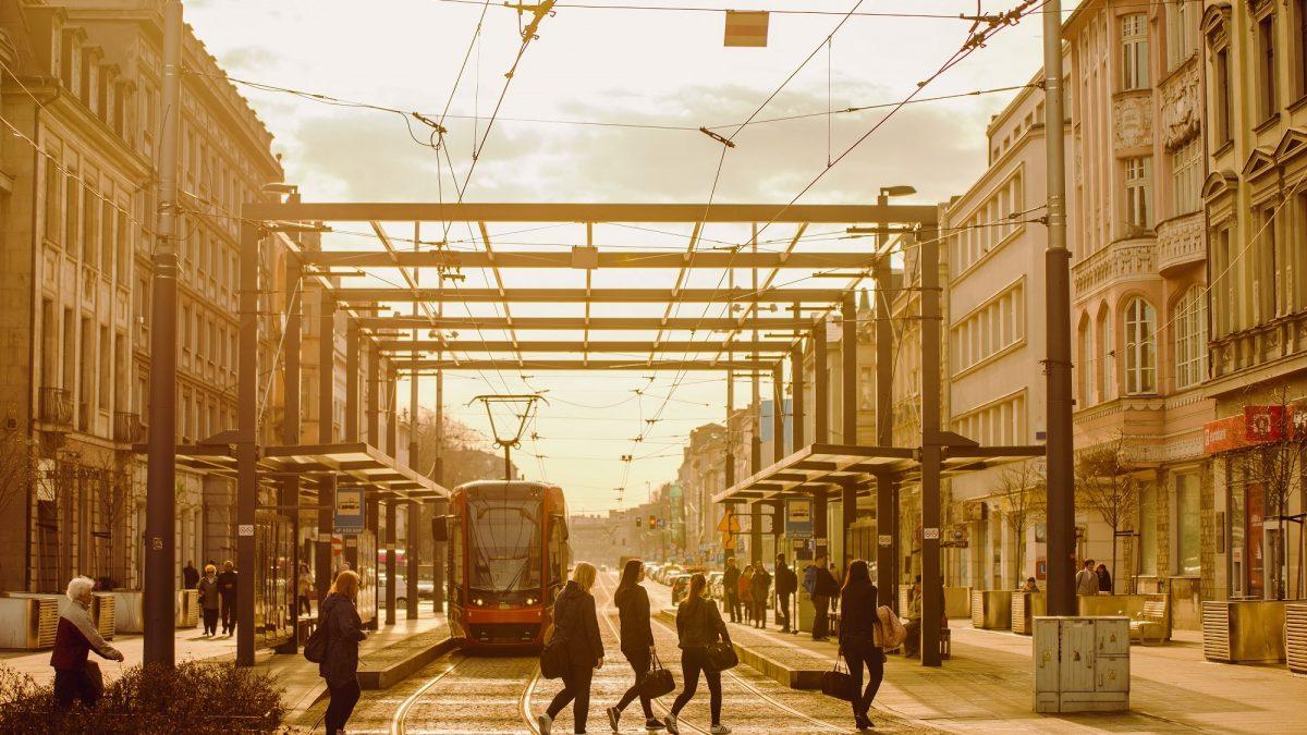 Przystanek tramwajowy z tramwajem i pasażerami