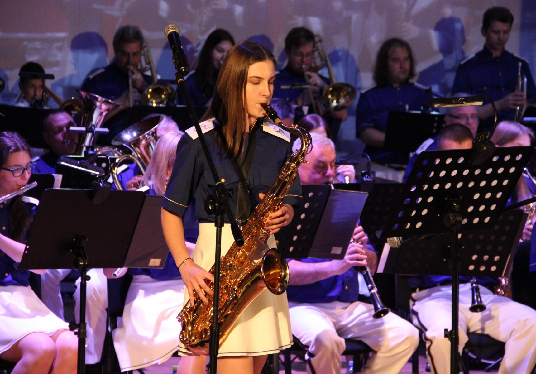 Kobieta grająca na saksofonie, w tle pozostali członkowie orkiestry