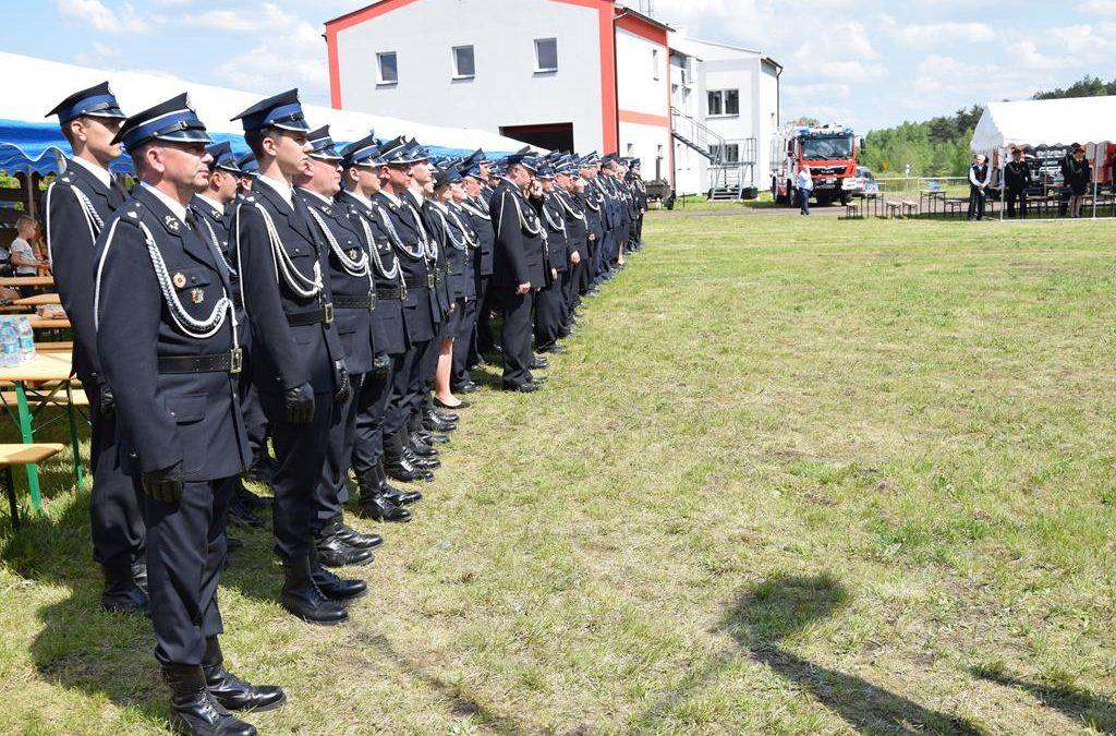 Strażacy w strojach galowych stojących obok siebie, w tle budynki i wóz strażacki