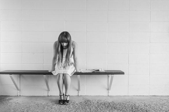 Samotna dziewczyna ze spuszczoną głową, siedząca na ławeczce