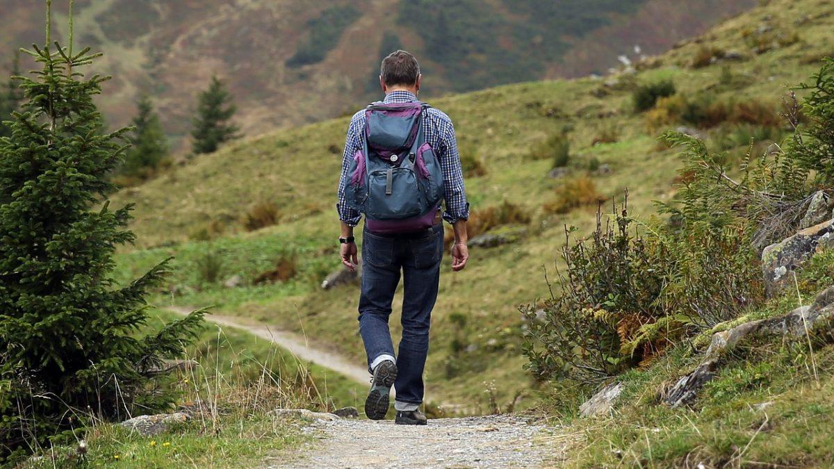 Turysta z aparatem fotograficznym idący przez góry