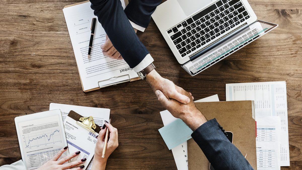 Biznesmeni podający sobie ręce nad stołem