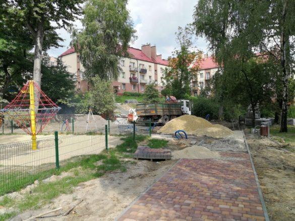 Na pierwszym planie remontowany chodnik, obok plac zabaw, w tel budyki