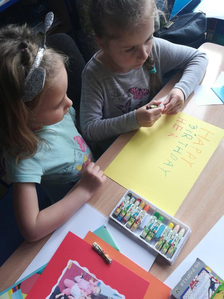 Dwie dziewczynki wykonujące kartkę urodzinową