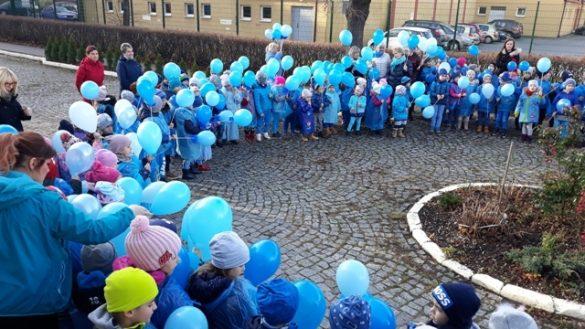 Dziecu w niebieskich ubraniach z balonami stoją na placu przedszkolnym