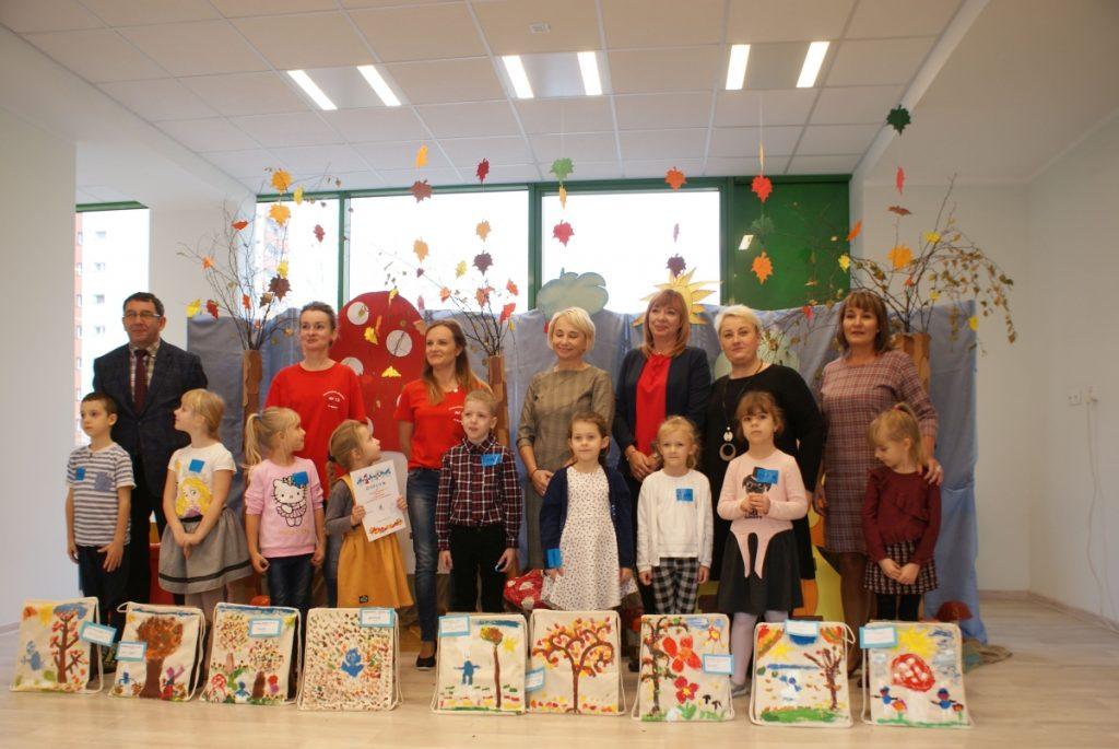 Zdjęcie grupowe dzieci wraz z dorosłymi, przed dziećmi ustawione prace plastyczne