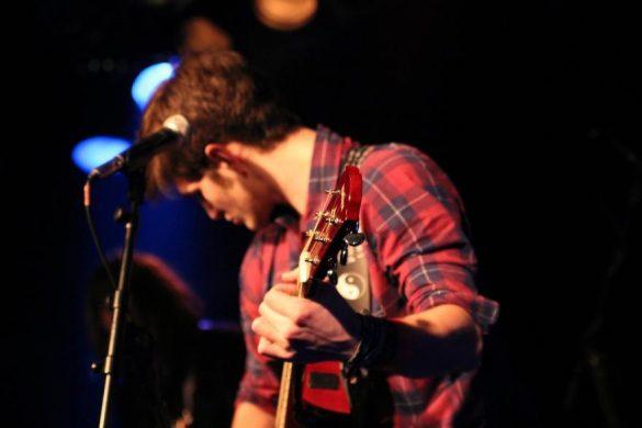 Muzyk z gitarą na scenie
