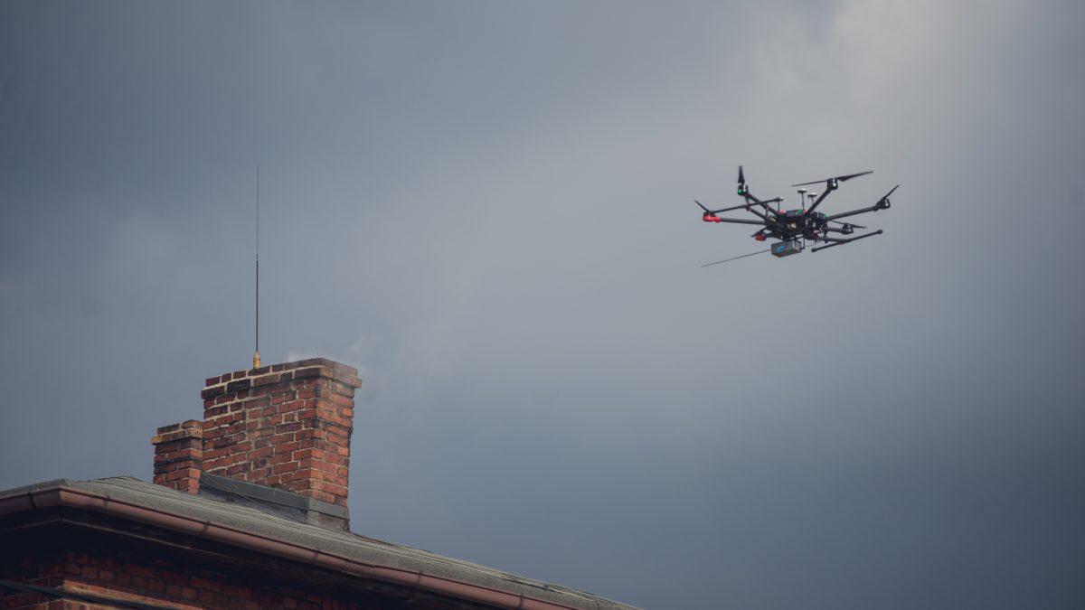 Dron latający nad kominem domu jednorodzinnego