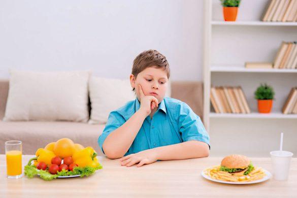 Młody chłopiec siedzący przy stole przed dwoma posiłkami: talerzem warzyw oraz hamburgerem. Na twarzy chłopca widoczny jest grymas zastanowienia. Swój wzrok kieruje w stronę hamburgera.