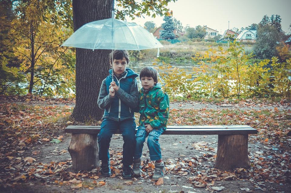 Dwóch chłopców siedzących z parasolem na ławce
