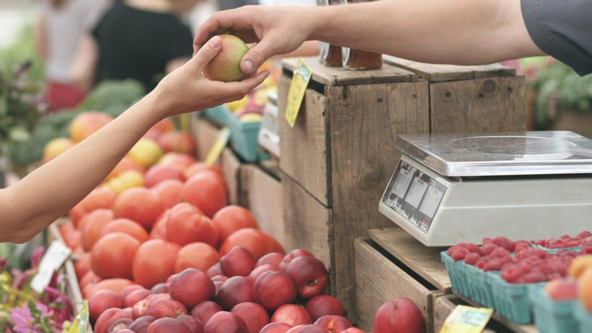 Sprzedawca podający osobie kupującej jabłko na targu