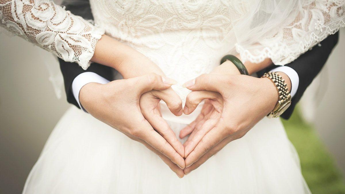 Dłonie młodej pary splecione w znak serca