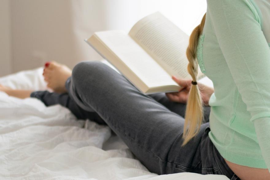 Dziewczyna w sypialni czytająca książkę