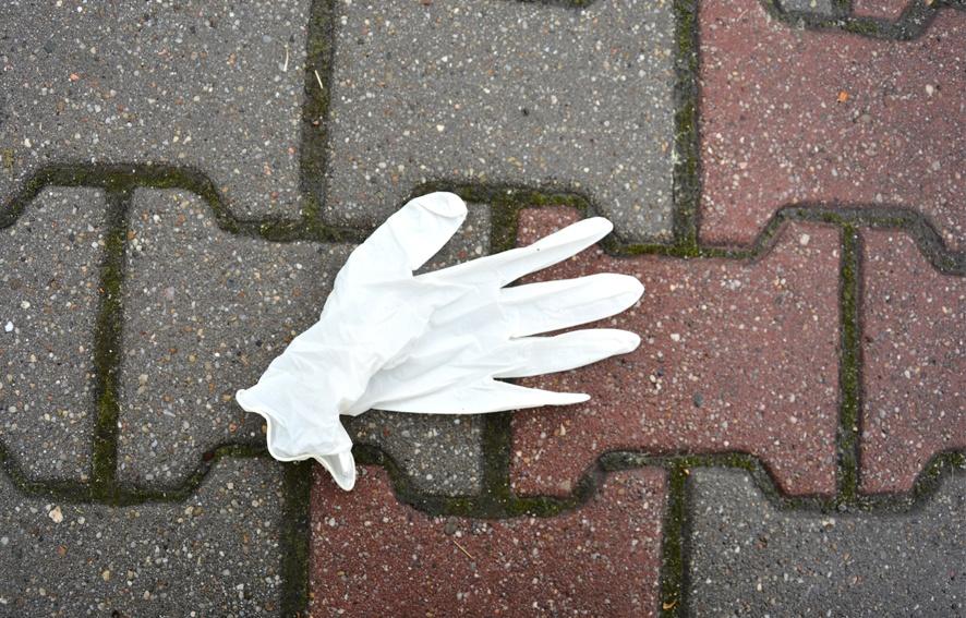 jednorazowa rękawiczka na chodniku