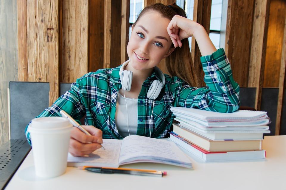 dziewczyna siedząca przy zeszytach i książkach