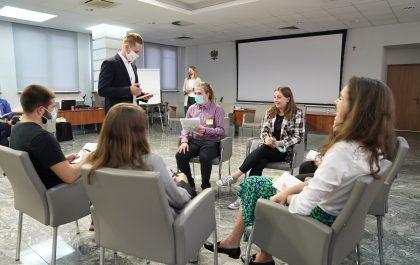 """Uczestnicy projektu """"Młodzi robią Metropolię"""" siedzą w okręgu i pracują w grupie"""