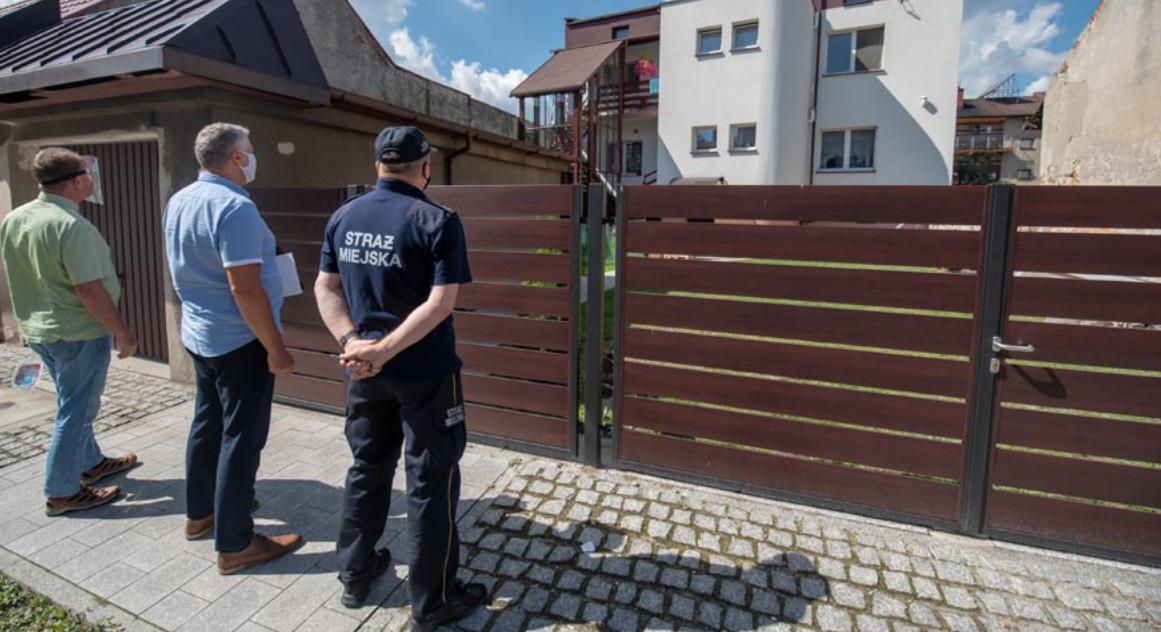 Urzędnicy i strażnik miejski przed prywatną posesją