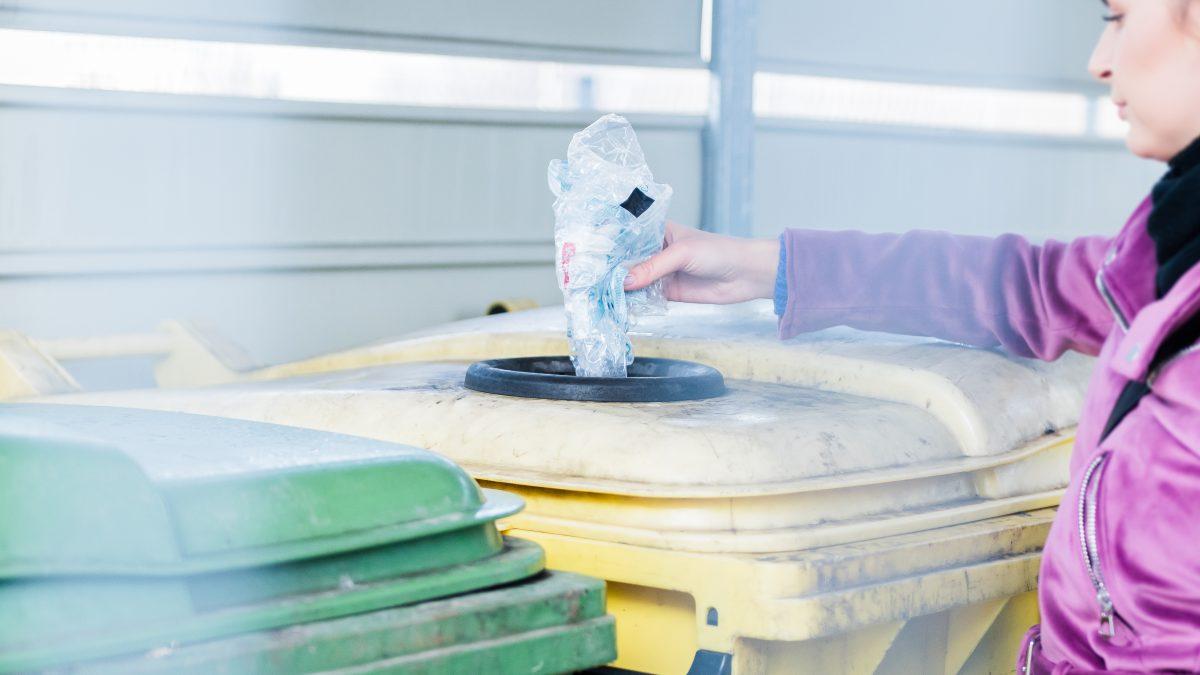 Dziewczyna wrzuca posegregowane odpady do śmietnika