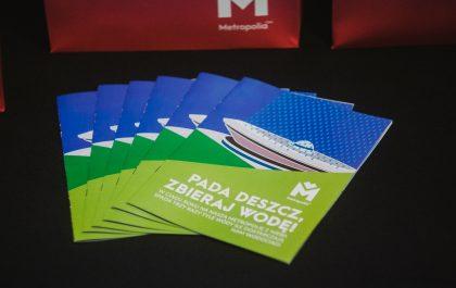 """Kilka egzemplarzy broszury """"Pada deszcz. Zbieraj wodę"""", a w tle fuksjowa pufa z logiem Metropolii"""