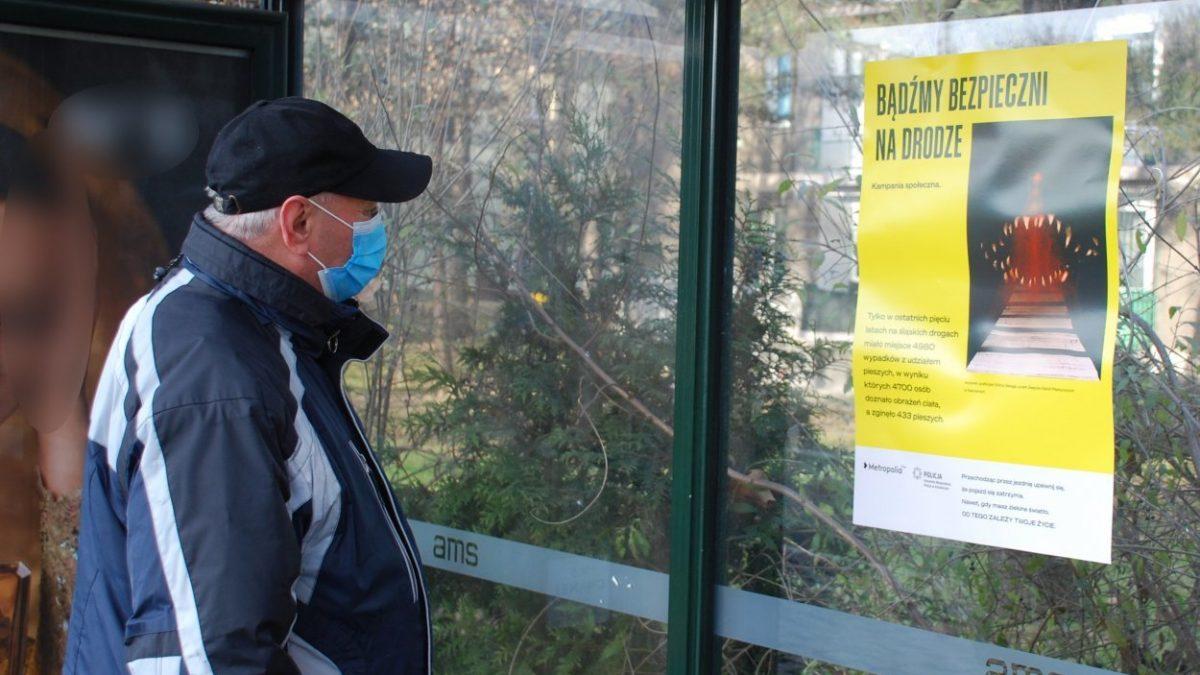 Pasażer ogląda plakat o bezpieczeństwie pieszych