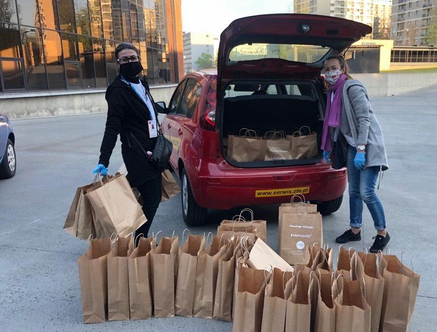 Dwie wolontariuszki pakują torby ze śniadaniem wielkanocnym do bagażniku samochodu