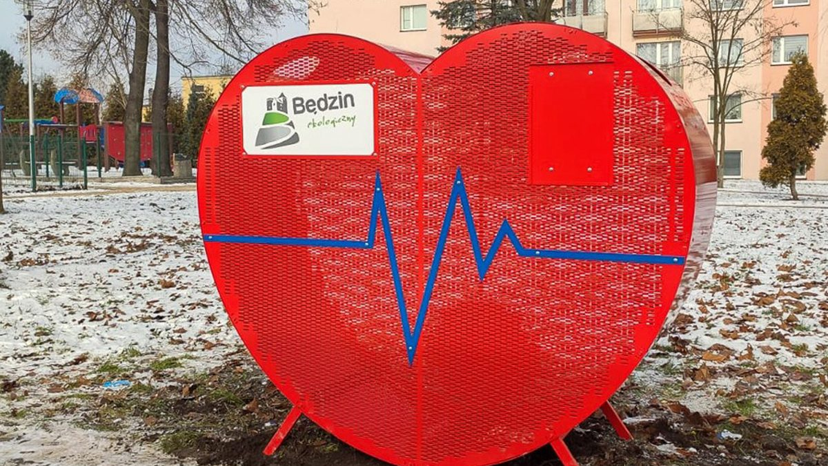 Pojemnik w kształcie czerwonego serca na nakretki ustawiony na osiedlu