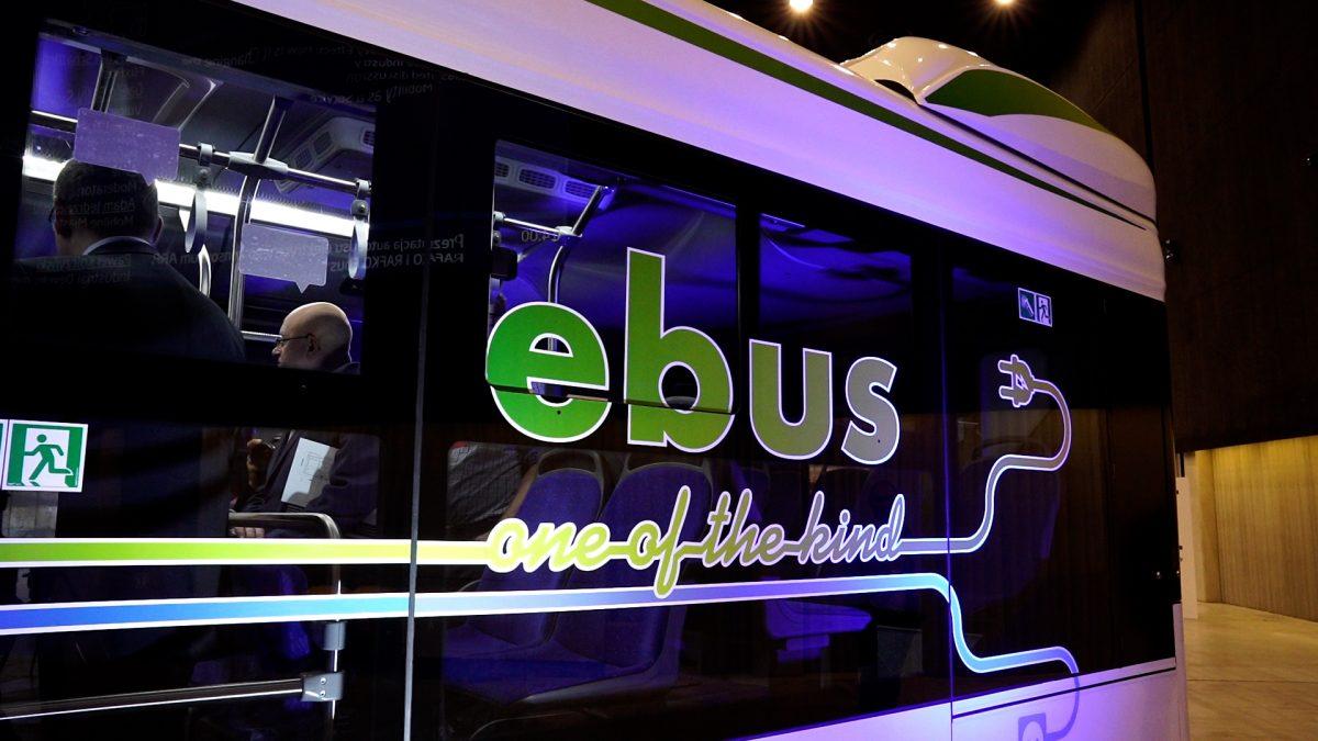 Zdjęcia przedstawia bok elektrycznego autobusu, na którego szybie znajduje się napis