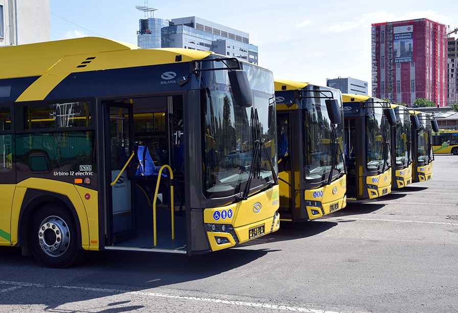Pięć autobusów elektrycznych w żółtym kolorze, które ustawione są w szeregu na płycie zajezdni