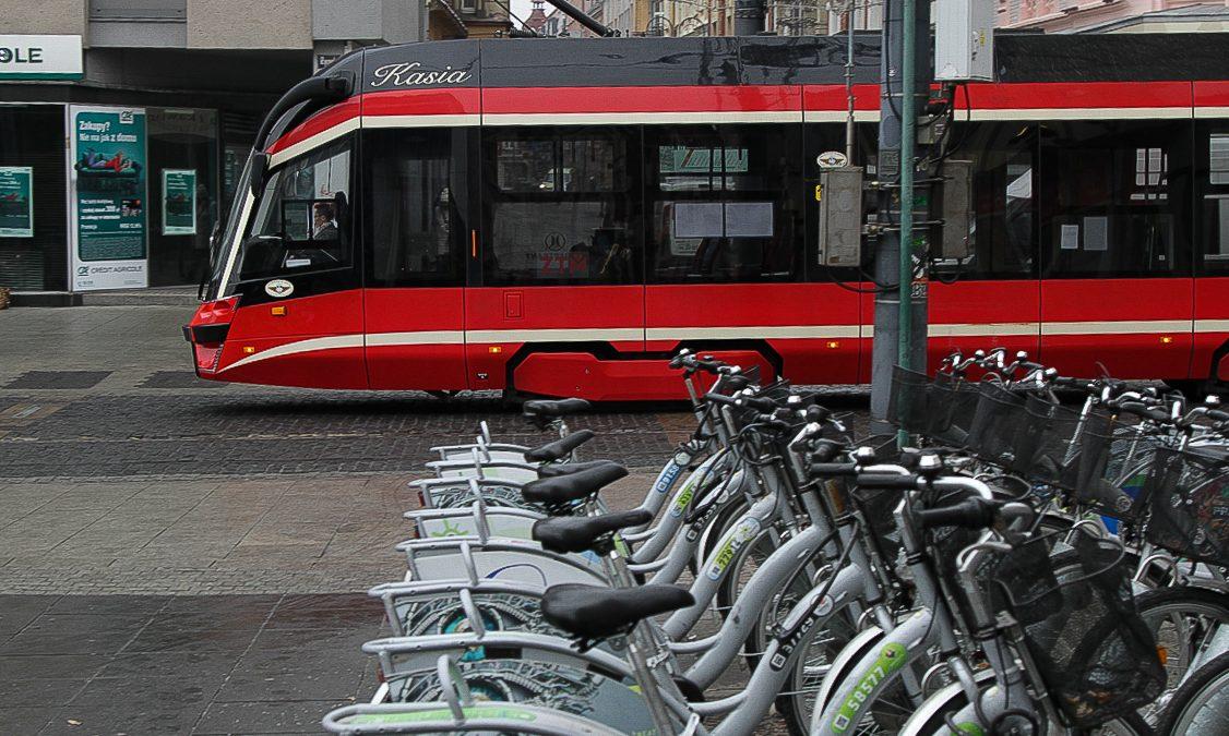 Rynek w Katowicach. Na pierwszym planie stacja rowerów miejskich. Drugi plan- przejeżdżający tramwaj