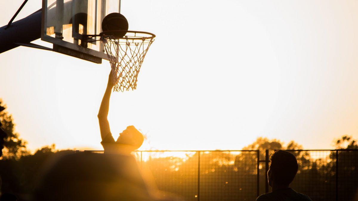 Gra w koszykówkę o zachodzie słońca. Zzawodnik wbija piłkę.