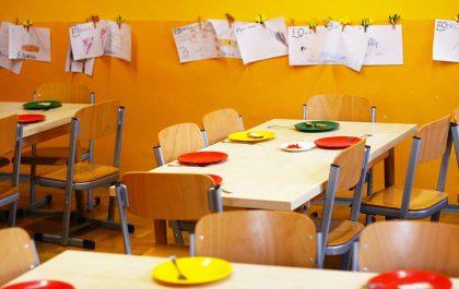 Wnętrzez przedszkola. Zdjęcie stolików i obrazków na ścianie.