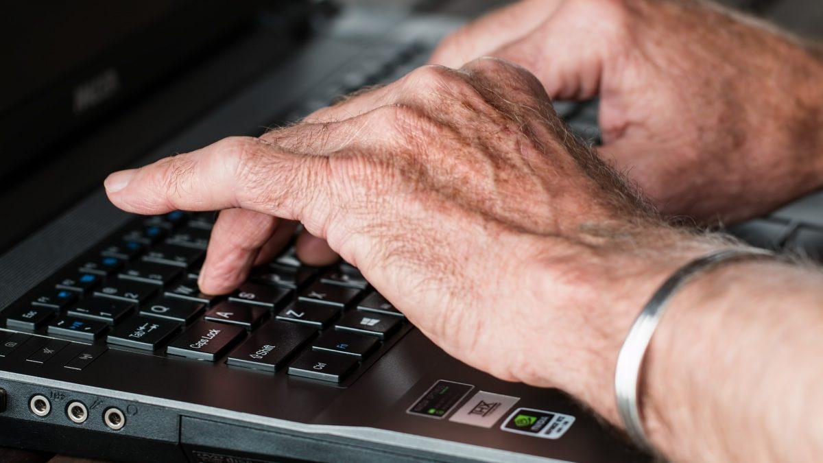 Zbliżenie na dłonie seniora, który pisze na klawiaturze laptopa