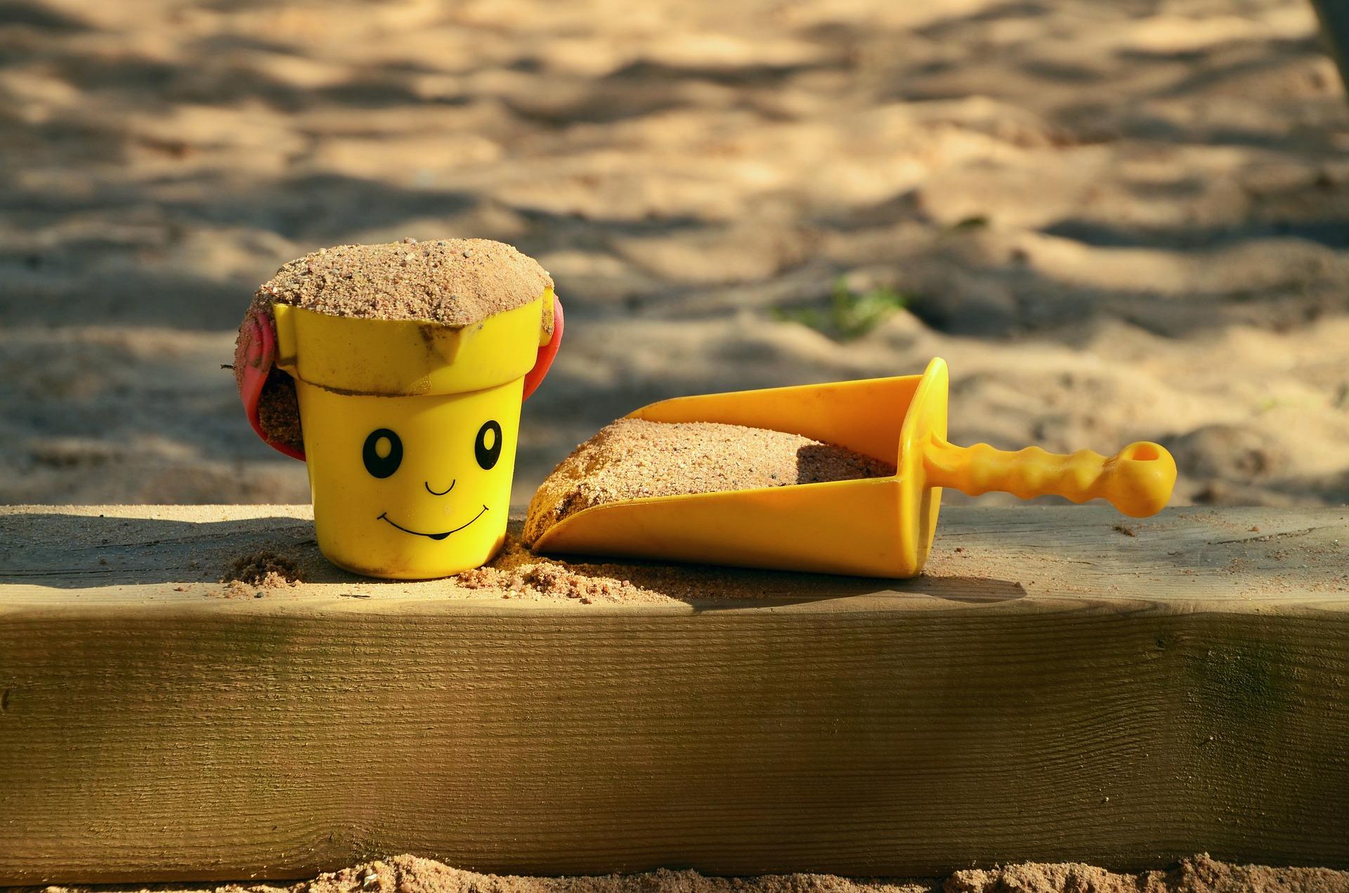 Zbliżenie na plastikowe wiaderko oraz łopatkę w piaskownicy