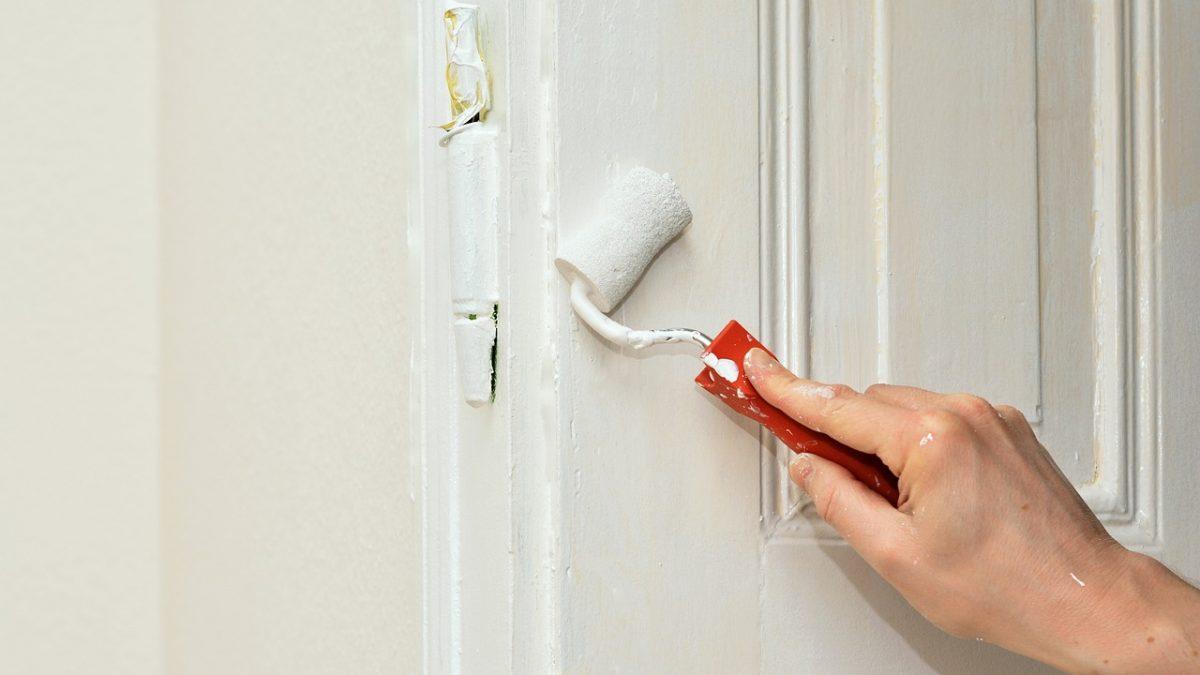 Zbliżenie na rękę i rolkę na farbę podczas malowania drzwi