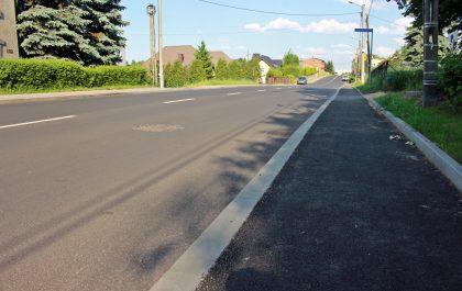 yremontowany odcinek ul. Wyzwolenia - asfaltowa jezdnia, asfaltowy chodnik, w tle niebo, zabudowania i zieleń.