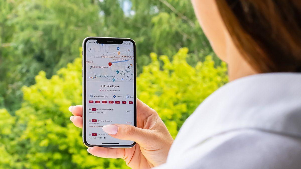 Kobieta trzyma w ręku telefon z wyświetlonym rozkładem jazdy w google map