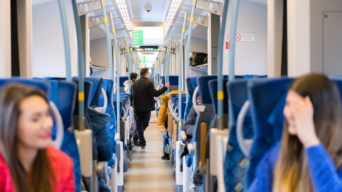 Środek wagonu kolejowego z pasażerami