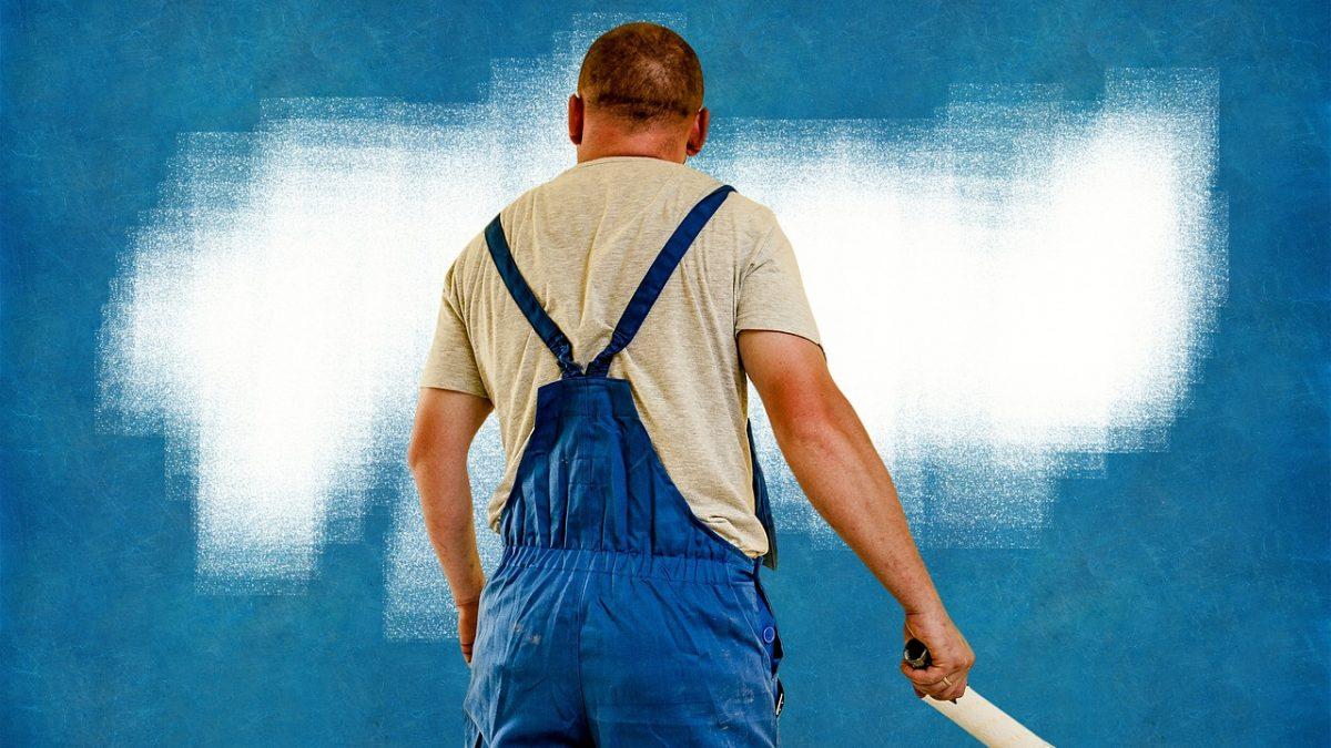Malarz w trakcie malowania ściany