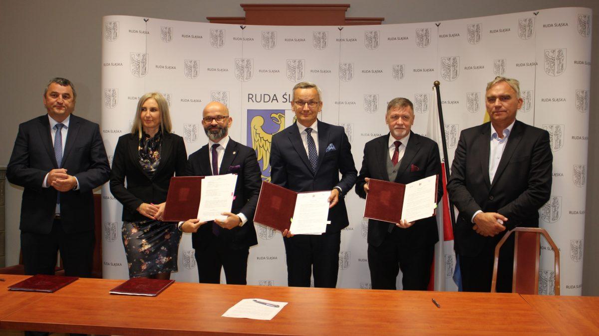 Grupa osób stojących za stołem, w tym trzech mężczyzn prezentujących teczki z podpisanymi dokumentami, w tle ścianka z herbem Rudy Śląskiej oraz flagi Polski i miasta.