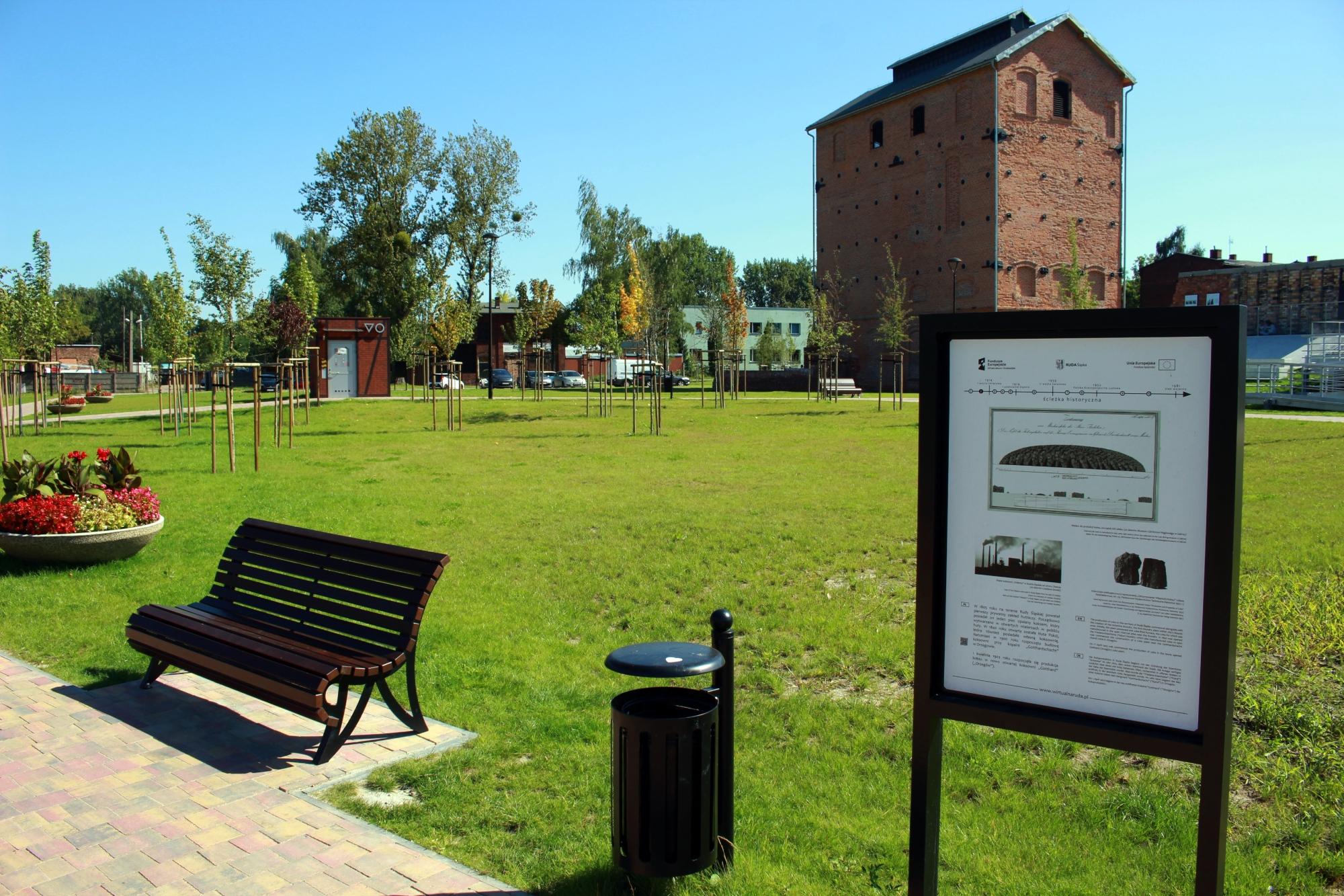 Kwietnik, ławka, kosz na śmieci i tablica informacyjna, w tle trawa, duży budynek z cegły, dzrewa i niebo.