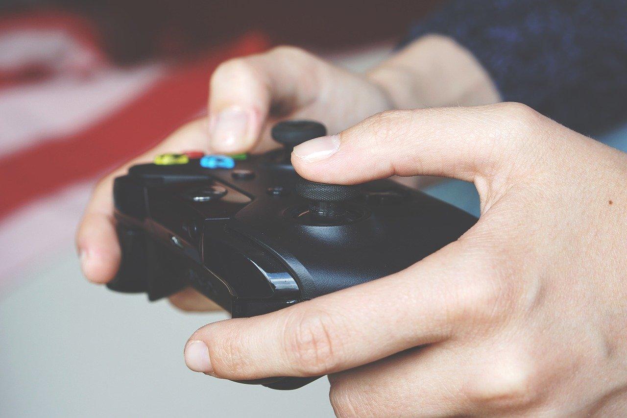 Dłonie trzymające kontroler do gier wideo