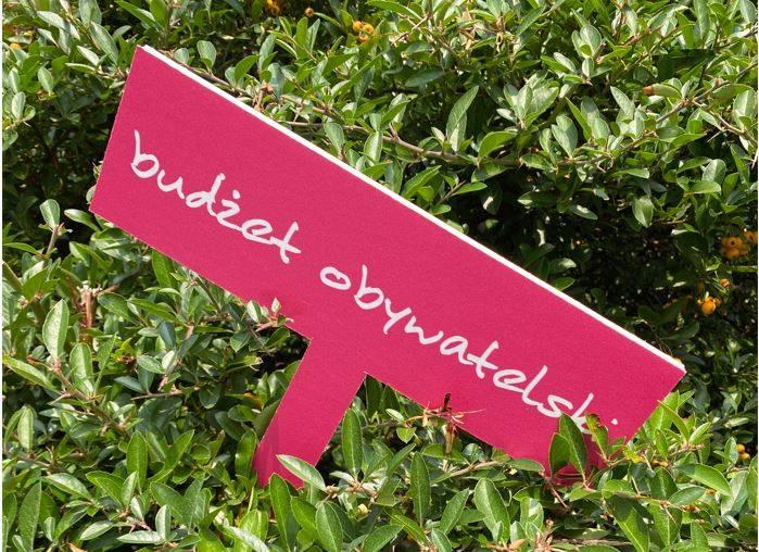 Tabliczka w kwietniku z napisaem: Budżet obywatelski